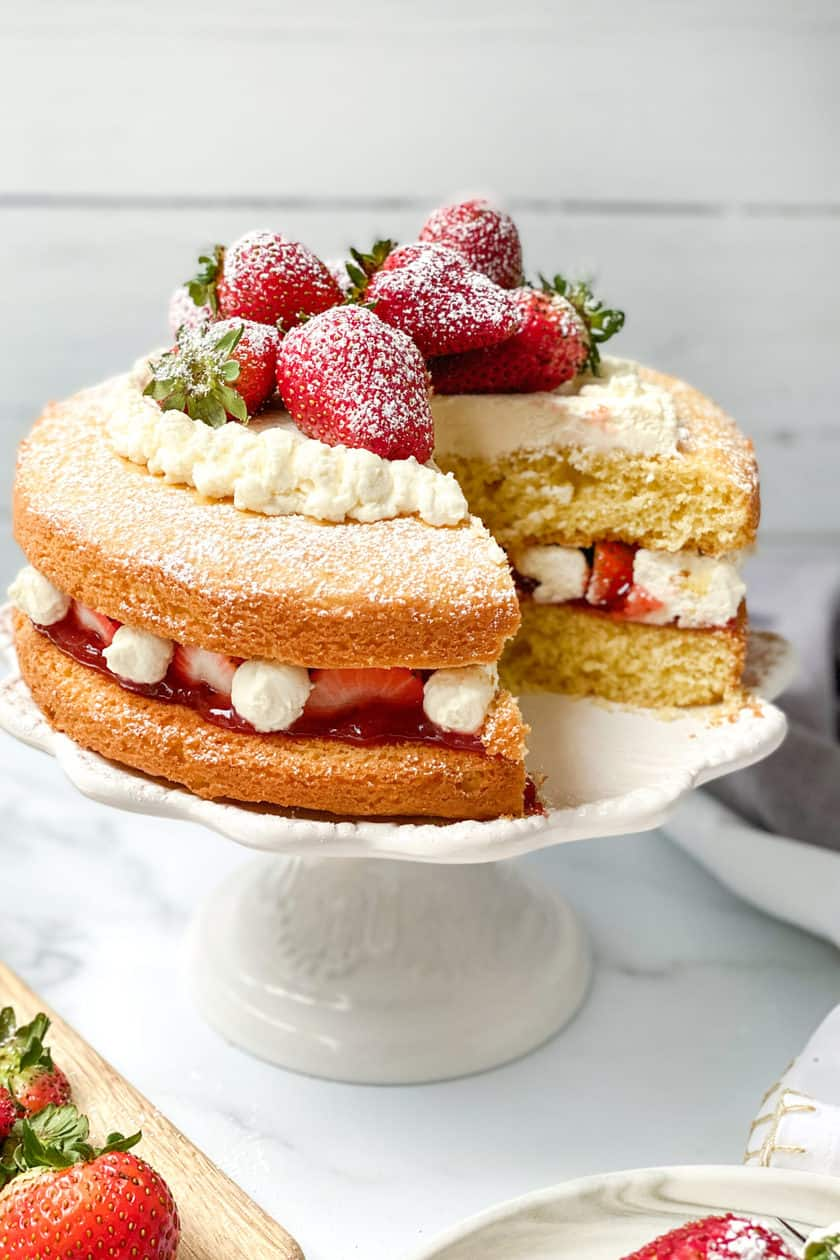 Victoria Sponge Cake with a slice missing on a white cake stand.