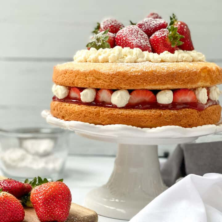 A simple, 2 layer Victoria Sponge Cake, layered with fresh strawberries and cream.