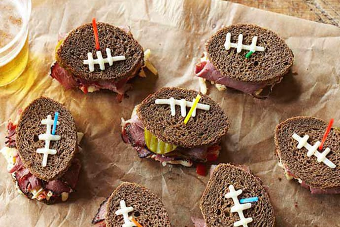 Ruben sandwiches cut into football shapes for Super Bowl Snacks
