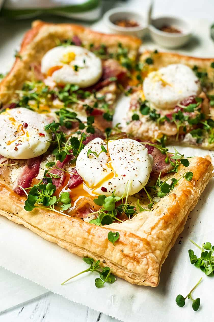 closeup view of poached egg on top of the puff pastry breakfast tart
