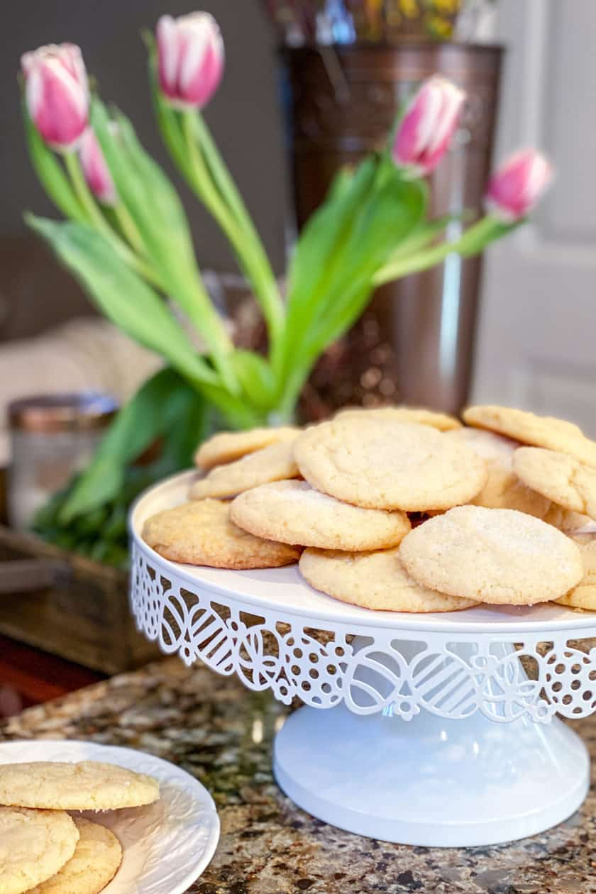 Lemon Sugar Cookies on a cakestand on my kitchen counter with tulips in the background.