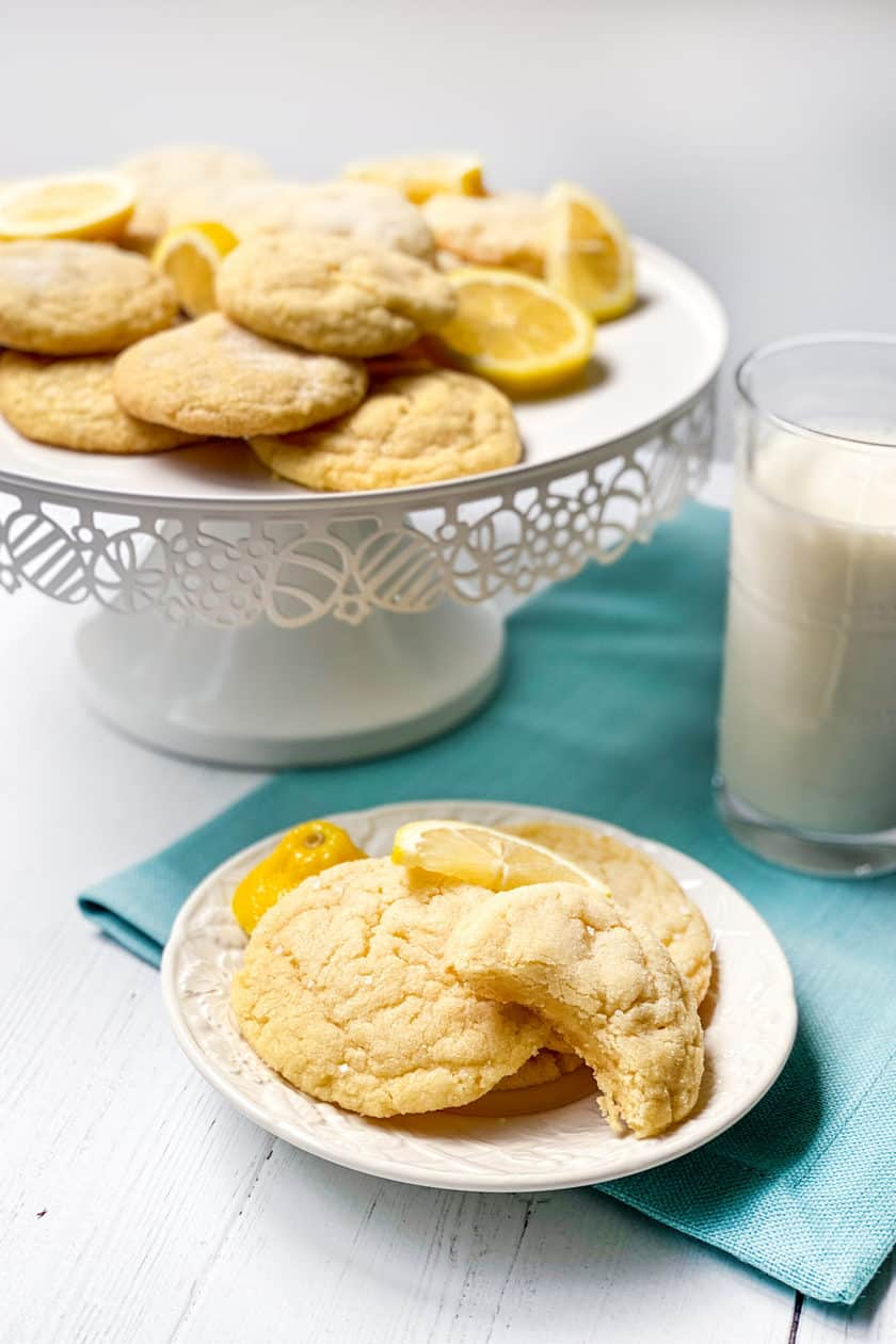 Long view of Lemon Sugar Cookies with milk on a turquois cloth napkin