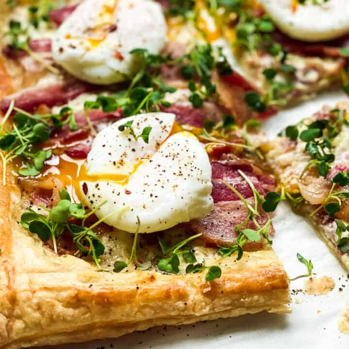 Closeup view of poached egg on a breakfast tart with bacon