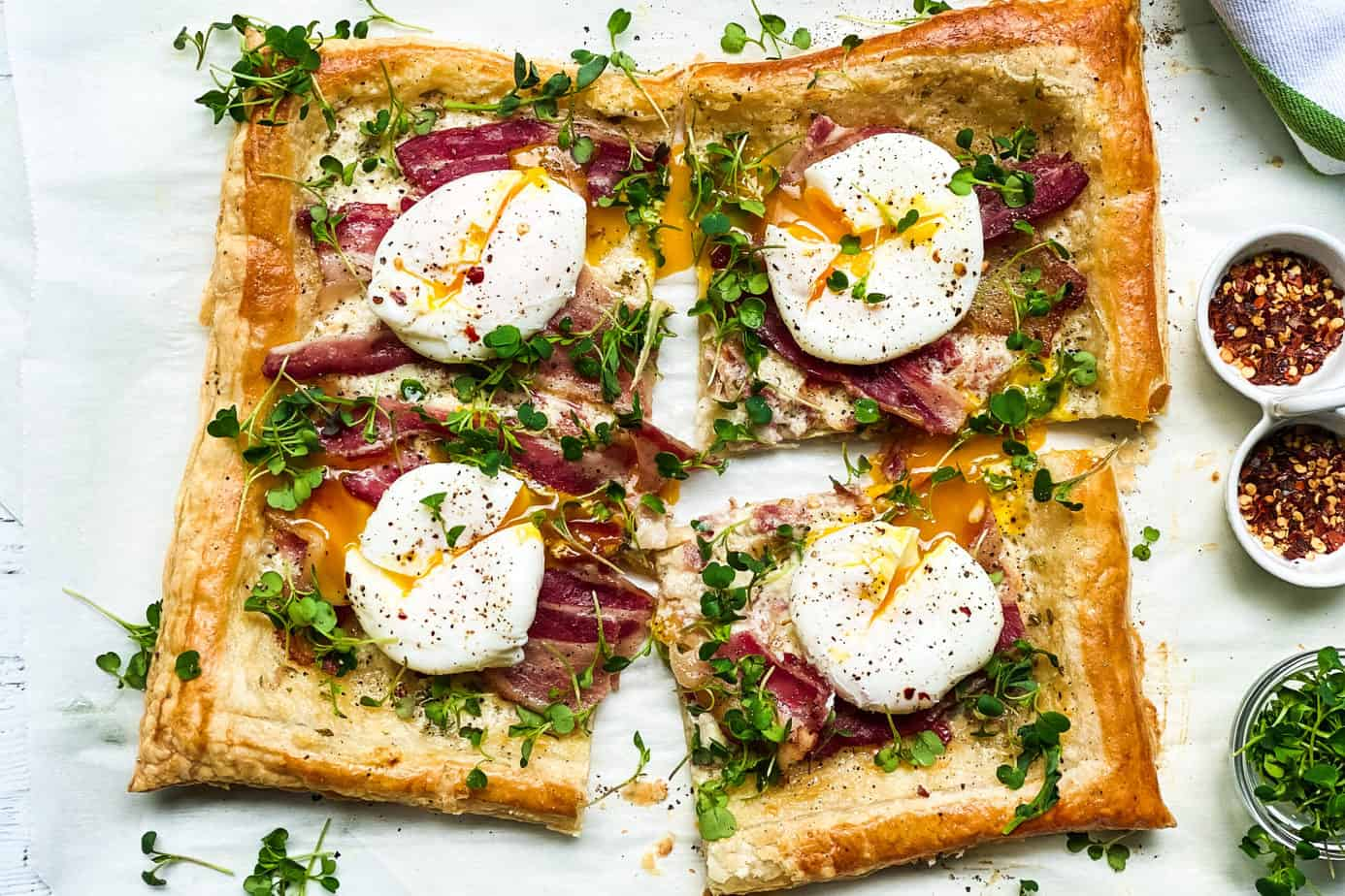 Breakfast Tart cut into 4 servings with puff pastry, poached eggs and bacon