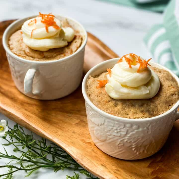 2 Carrot Cake Mug Cakes Topped with Whipped Cream Cheese on a Wood Serving Board