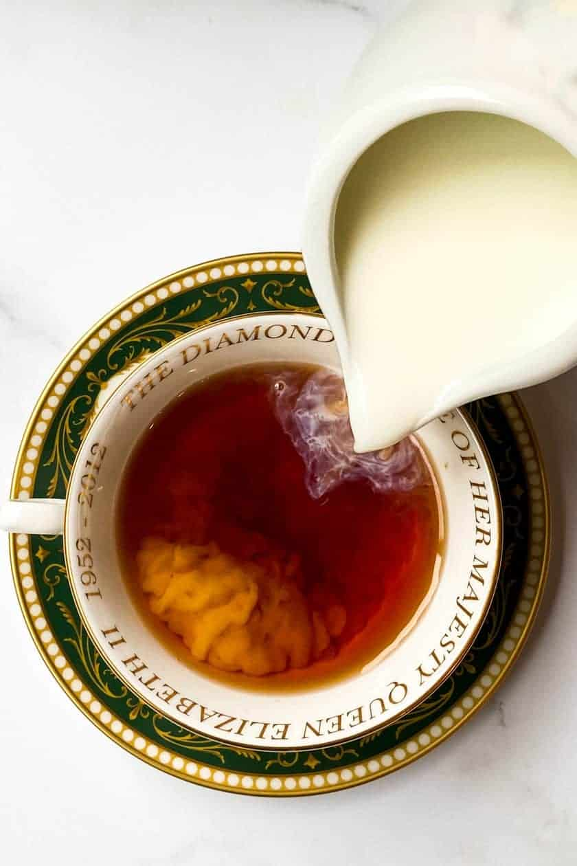 Milk pouring into a teacup filled with Irish Breakfast Tea