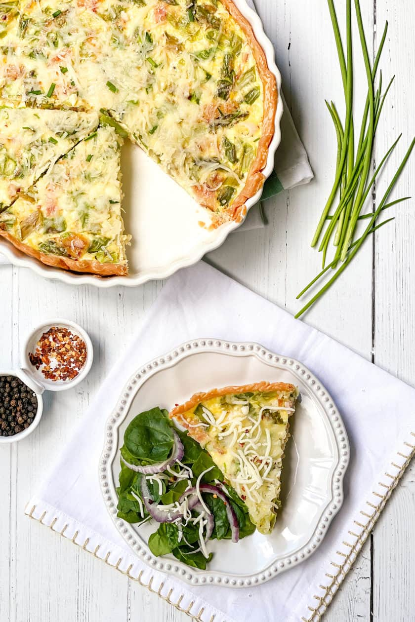 Slice of Asparagus Quiche on a White Scalloped Plate