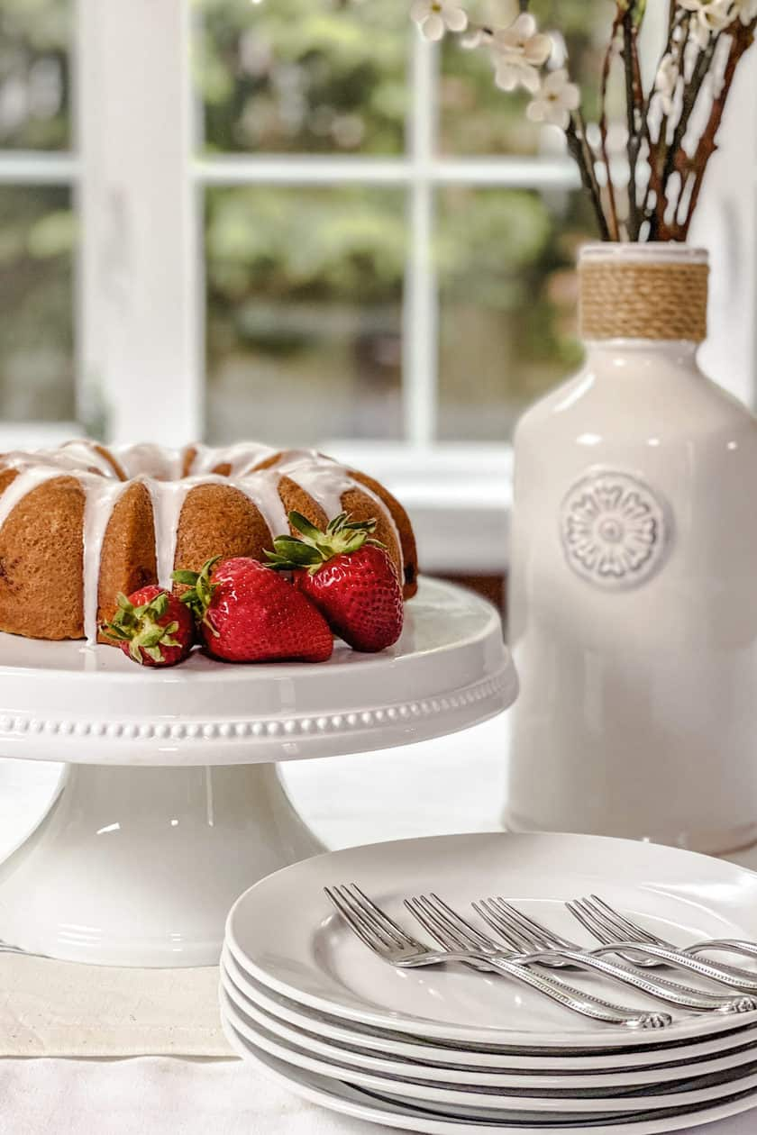 Side view of Strawberry Bundt Cake with Lemon Glaze on a White Cake Stand