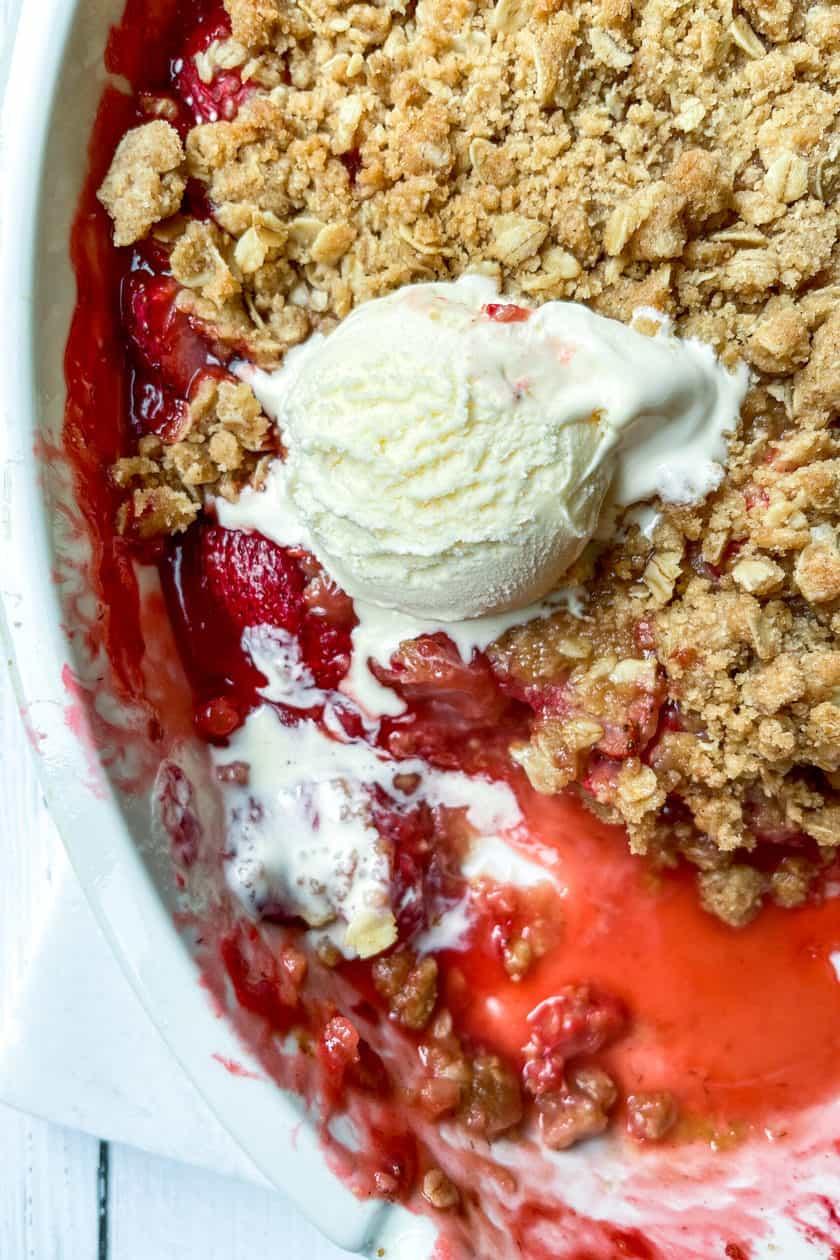 Closeup view of Strawberry Crisp with vanilla ice cream.