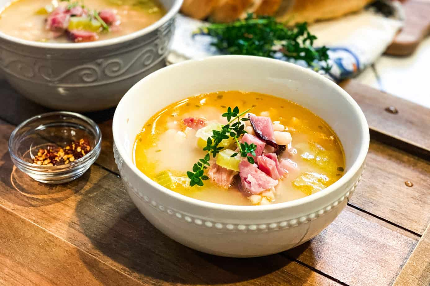 Ham Bone Soup in a White Bowl with Ham and Fresh Thyme