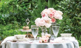 A teatime table for 2 in the garden with pink roses