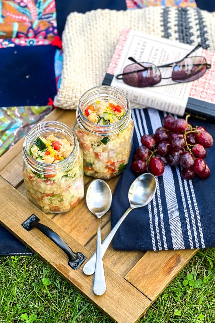 Quinoa Salad in mason jars with grapes and a picnic basket