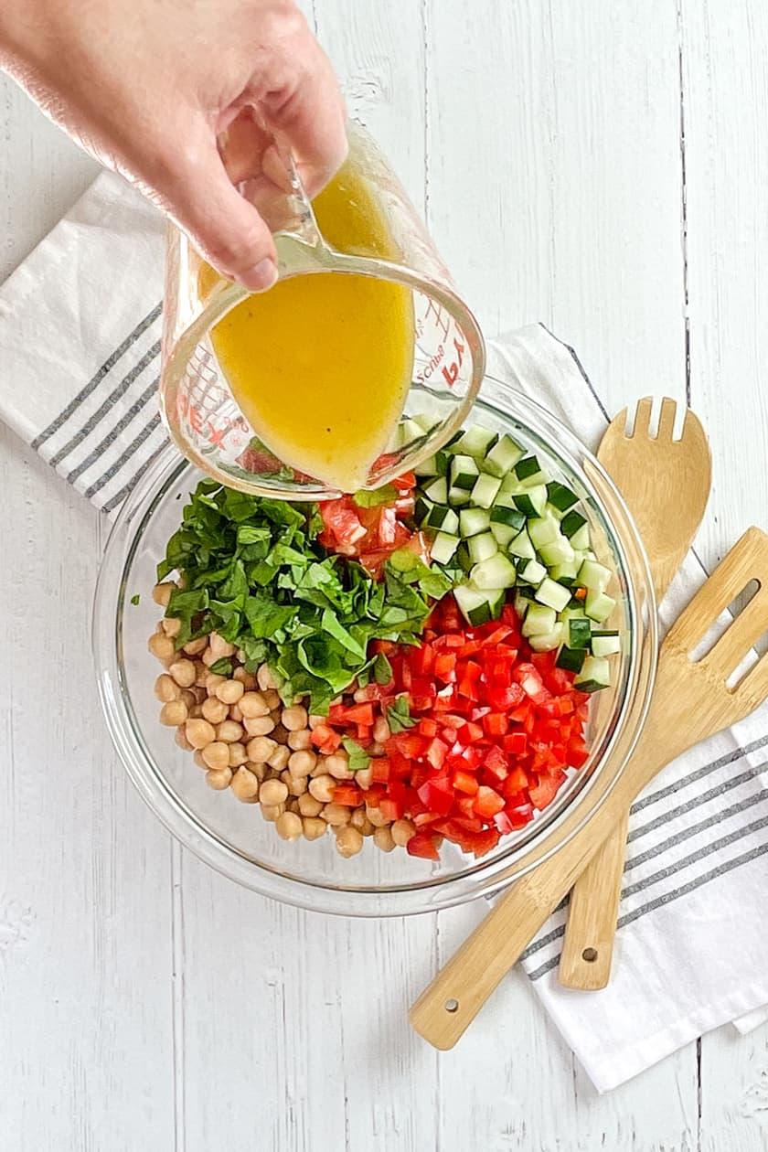 Pouring Lemon Dressing over Quinoa Salad