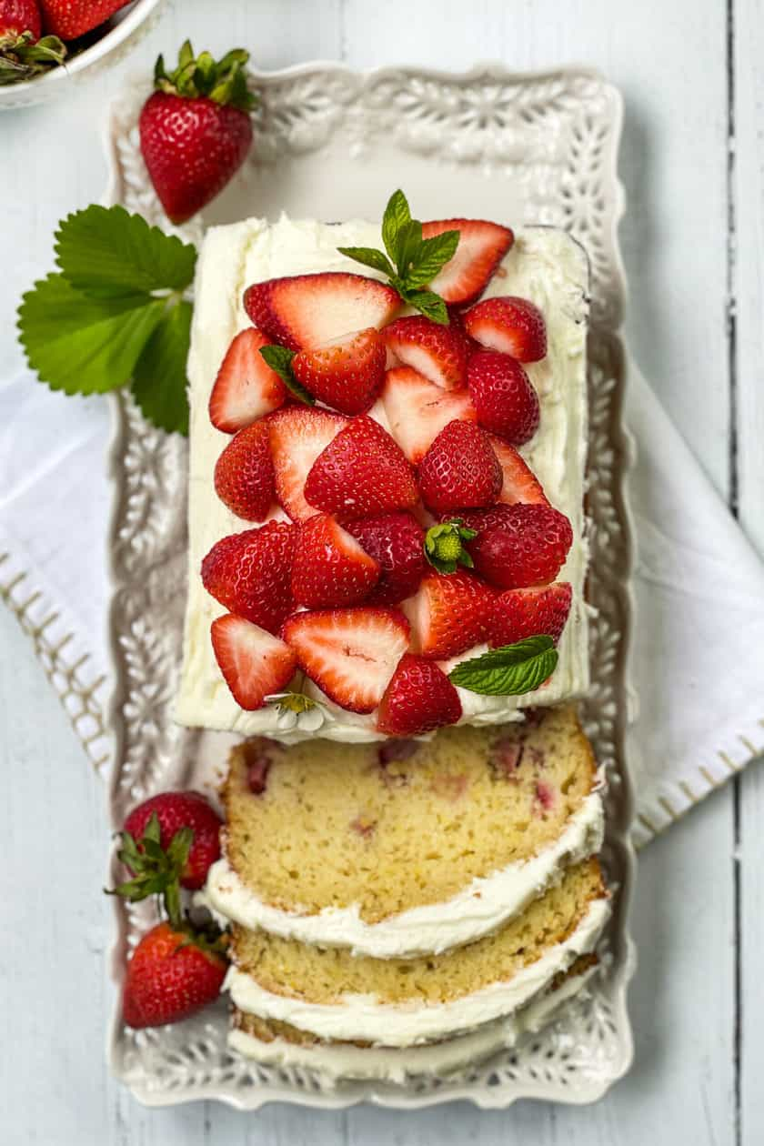 Top view of Strawberry Bread with sliced fresh strawberries and mint leaves