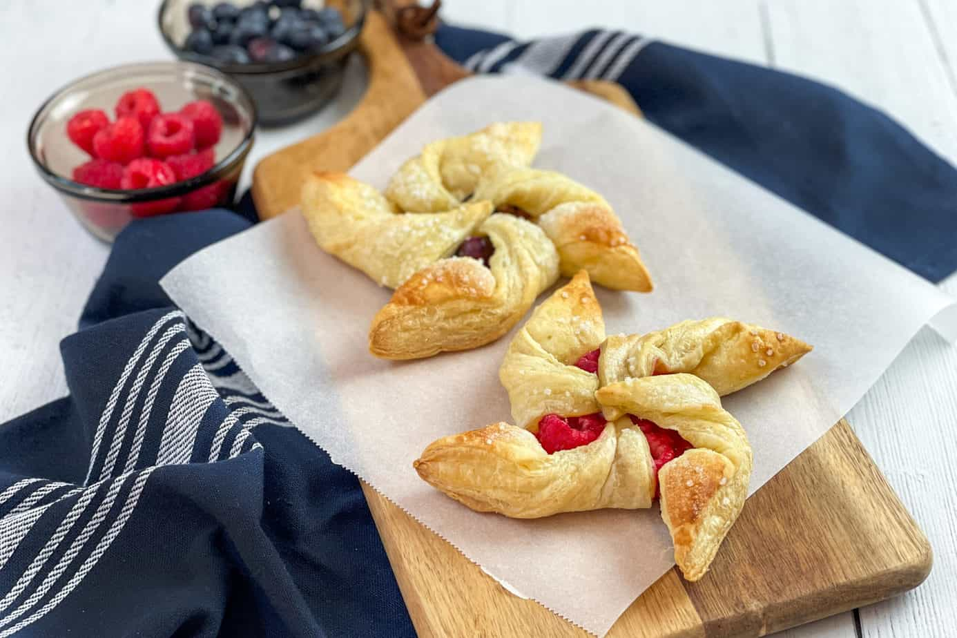 Two berry pinwheel pastries on a sheet of parchment paper with fresh raspberries and blueberries