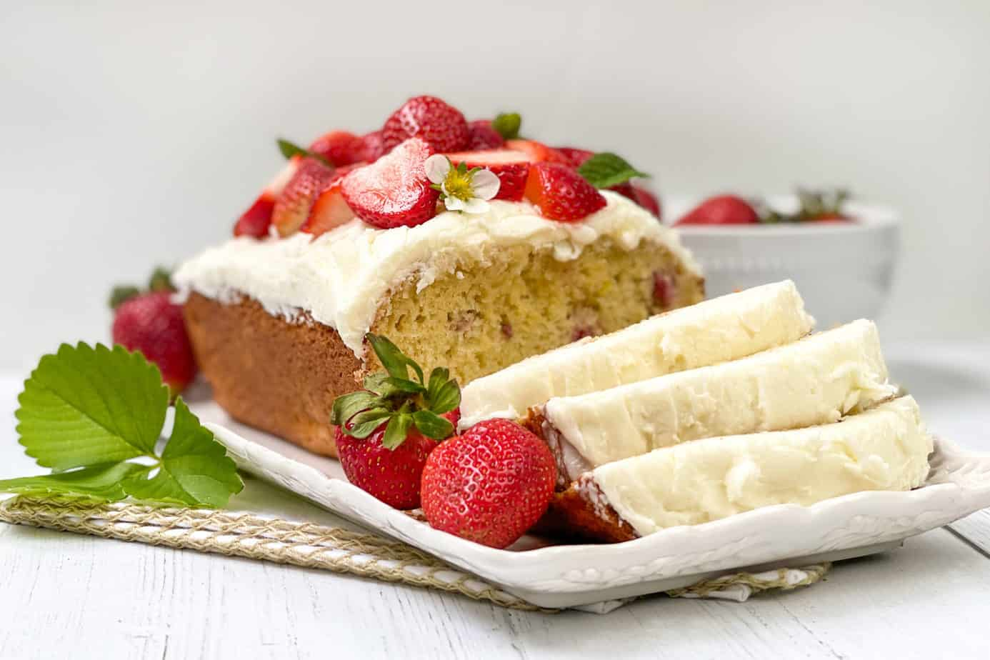 Sliced Strawberry Bread topped with fresh strawberries and icing.