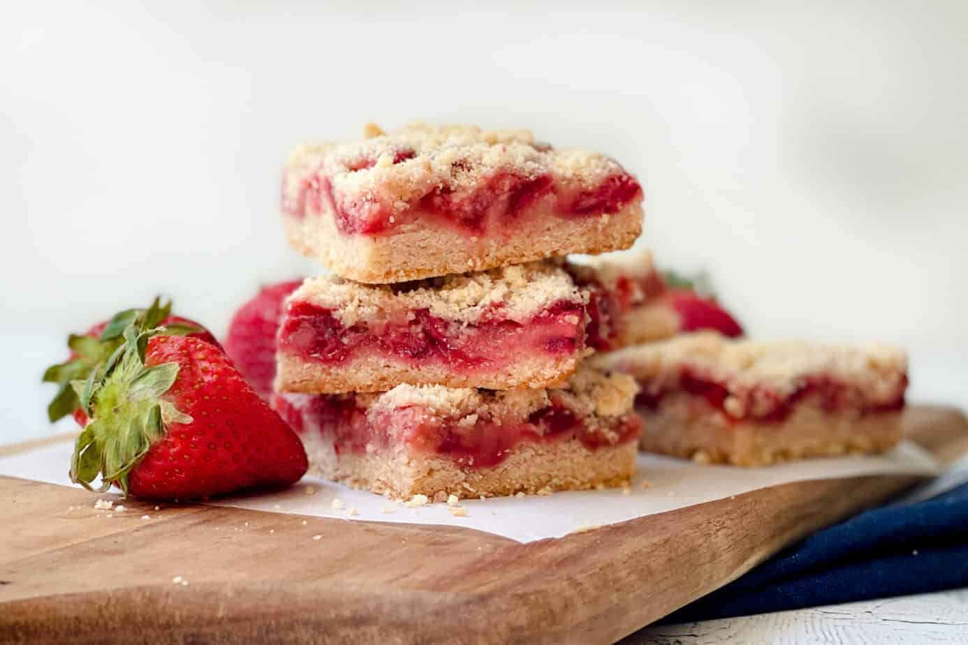 Stacked Easy Strawberry Crumble Bars on a wooden board