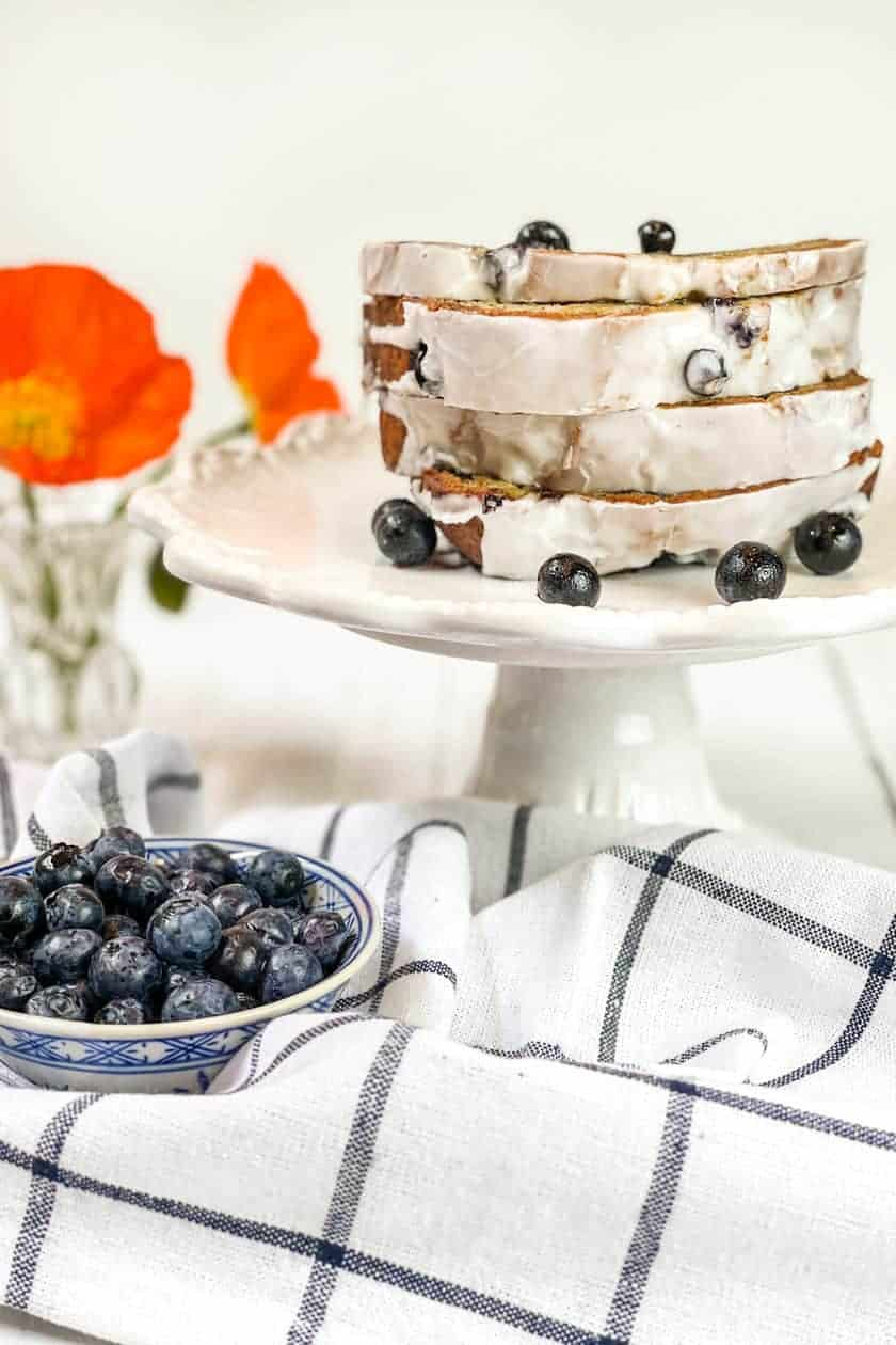 Sliced Blueberry Banana Bread on a platter with fresh blueberries and poppies