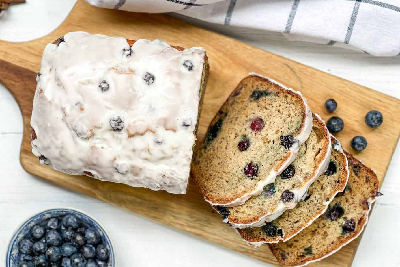 Sliced Blueberry Banana Bread on a wood cutting board with fresh blueberries.