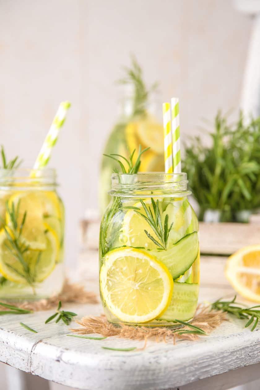 Herb Lemon Water in glass mason jars with yellow straws