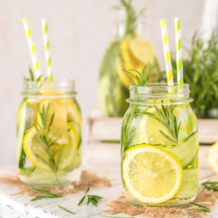 Glass jars of Herb Lemon Water with slices of cucumber, lemon, and fresh herbs