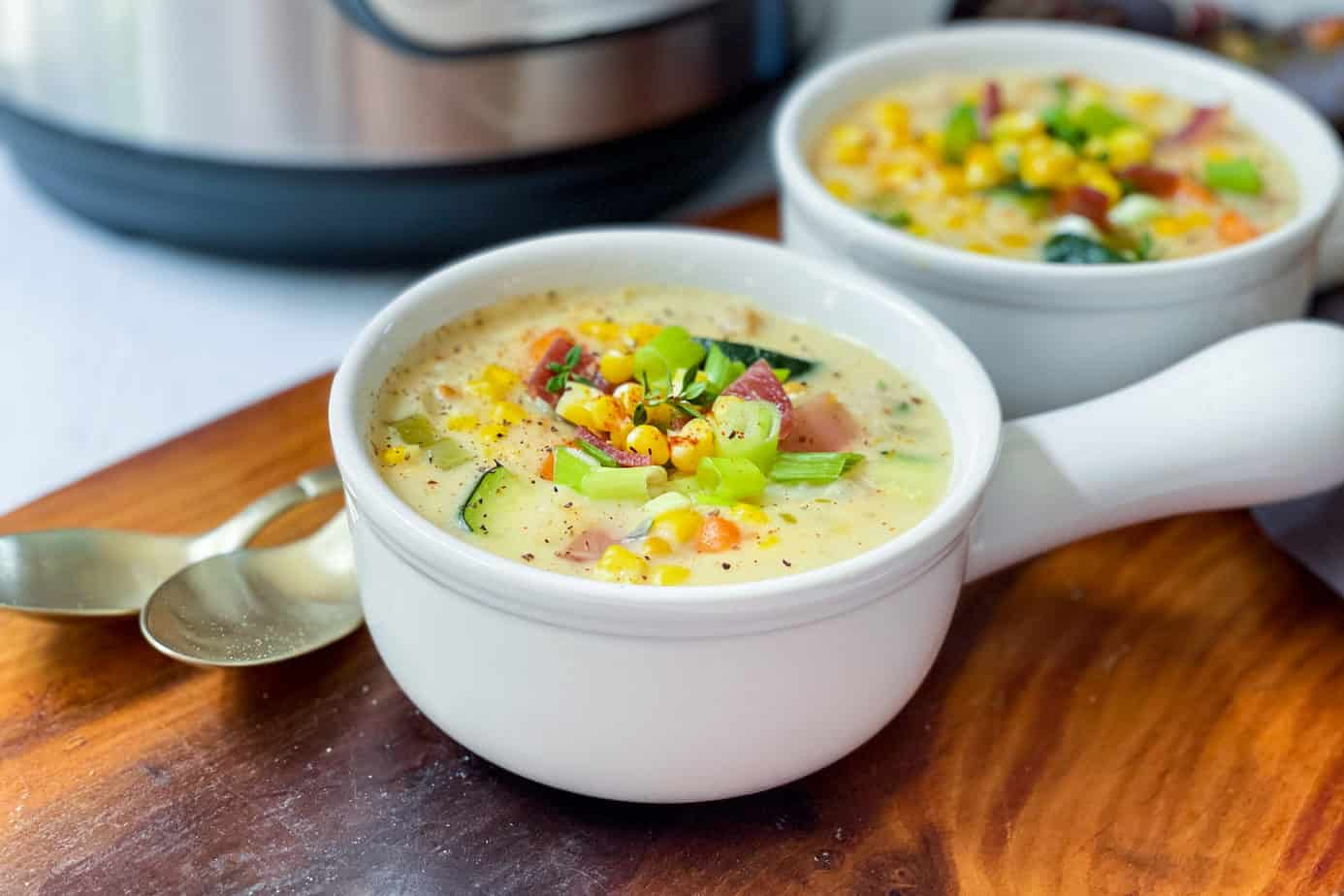 Two bowls of Zucchini Corn Chowder in soup bowls with handles