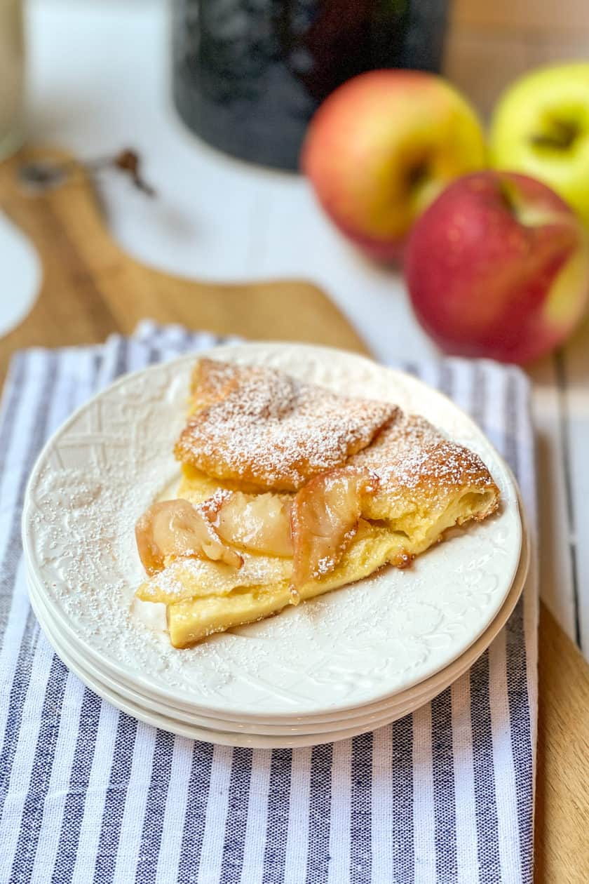 Wedge of Apple Dutch Baby on a white plate