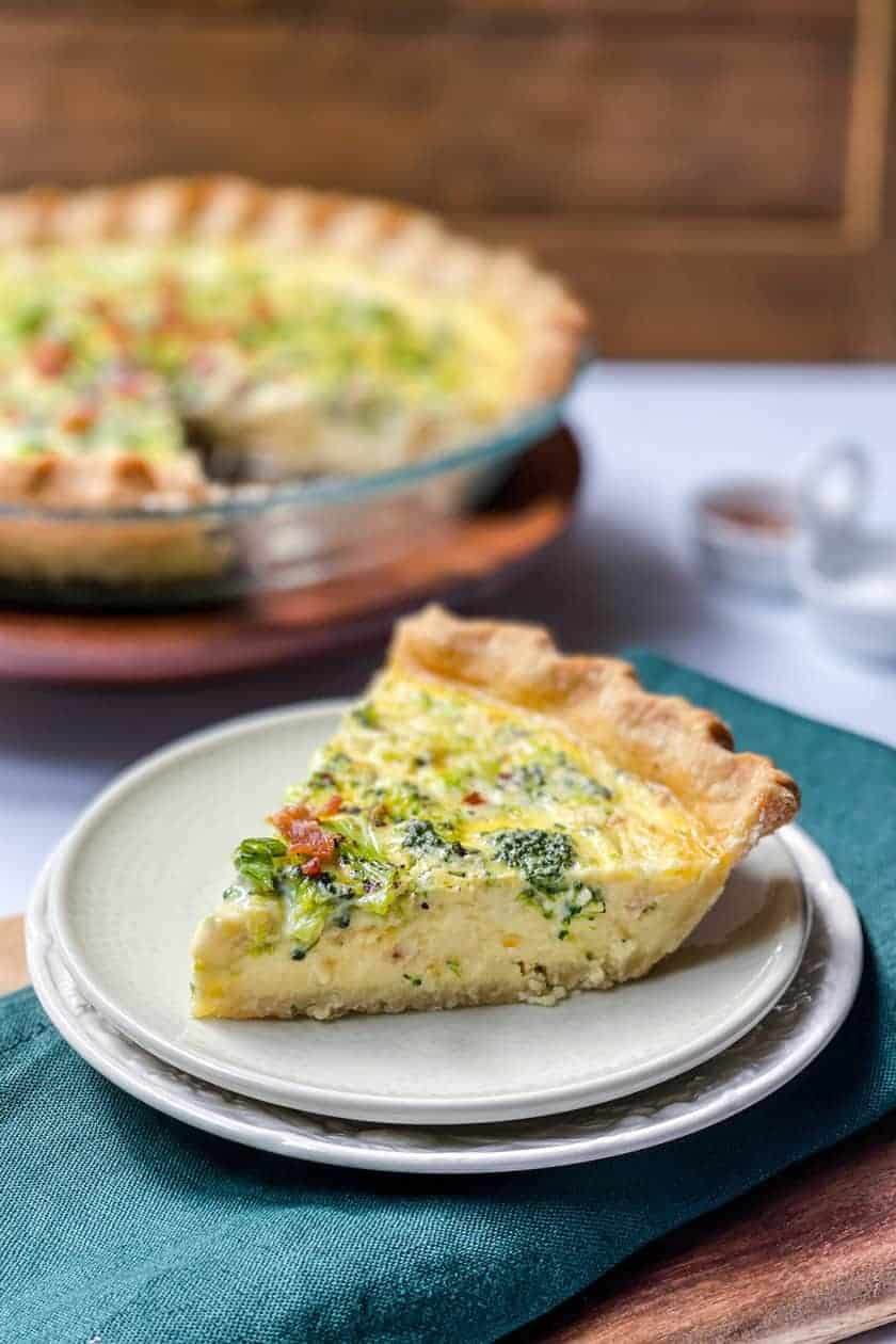 Side view of sliced Broccoli Cheddar Quiche with whole quiche in the background