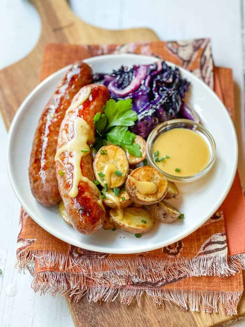 Vertical view of Sheet Pan German Bratwurst plated with roasted potatoes and red cabbage